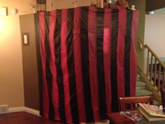 I made these to start making my circus tent covers for our CarnEvil party.  Used dollar store table cloths, cut into strips and glued them together alternating colors.