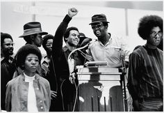 Black Panther Party co-founder Huey P. Newton (1942 - 1989) (center) smiles as he raises his fist from a podium at the Revolutionary People's Party Constitutional Convention, Philadelphia, Pennsylvania, early September 1970.