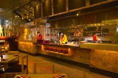 Open Restaurant Kitchen Designs use counters + glass walls to section off the kitchen in a mixed