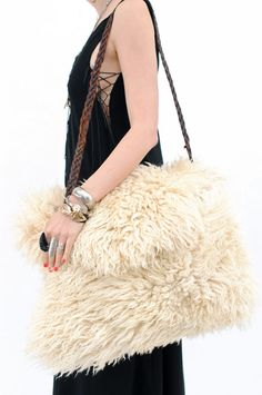 Amazing oversize Mongolian fur bag with braided vintage leather belt strap. Raw insides. Large front flap. No closure. Overall excellent condition. 17 in. x 21 in. - 17 in. handle drop.