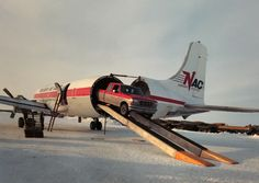34TA,  DC-6A swing tail belonging to Northern Air Cargo unloads a truck some where in Alaska.