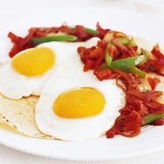 Sunny side up eggs welcome a warm, peppery tomato salsa in this version of a Mexican favorite.  Recipe: Huevos Rancheros with Spicy Ham Sofrito   - Delish.com