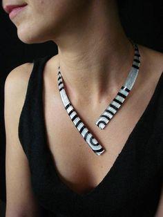 Bijoux de créateur (Artisan Joaillier) mêlant innovation technique, artisanat dart et design. Un collier Design, très léger, noir avec feuille dargent aux tonalité légèrement bleu irisé, pour une ligne épurée et un visuel terriblement graphique. Composés dune seule pièce, débarrassés de