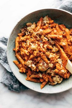 Red Pepper Cashew Pasta with Roasted Cauliflower on a grey plate.