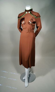 1930s ART DECO crepe afternoon dress with pleated silk satin and rhinestone trim. Cocoa brown drapey rayon crepe dress with brown and green pleated silk satin trims. Two-tone accordion pleated ruffle trim stands at neckline, layered at yoke and sleeve cap and brown pleated faux pockets at bust. Label: WAINWRIGHT FROCKS. Via RP Vintage.