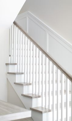 Staircase. The staircase features a clean, neutral look thanks to the square white spindles and white oak handrail and flooring.  Patterson Custom Homes. Brandon Architects, Inc.