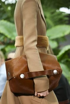 Camel, with fur and leather touches, with metal detail.  Mixed materials.