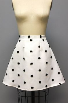 Flirt with your favorite boy with this cute cotton canvas mini-skirt with pom pom polka dots!  100% Cotton  Color: Black and White