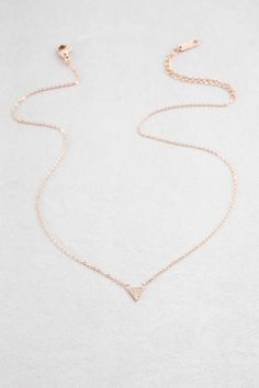 Triangle stone studded charm necklace in rose gold.