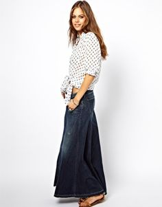 Denim maxi outfit idea #8. Wear a stiffer denim maxi skirt with a tied-at-the-bottom, rolled-sleeved button-down and sandals.