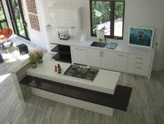 White kitchen with dark table height bar seating, and vein cut stone floor and pony wall.