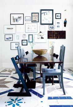 Prachtig Scandinavisch interieur met blauwe accenten. Ik weet niet wat ik het mooist aan deze foto vind. Eigenlijk vind ik namelijk alles wel mooi. De verzameling fotolijsten, de oude letterbak en de eettafelstoelen. En dan heb ik nog niet eens de houten beschilderde vloer genoemd!