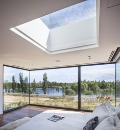 An immense skylight and walls of glass provide amazing views of the clouds and surrounding Limay river in this home located in Patagonia Argentina.