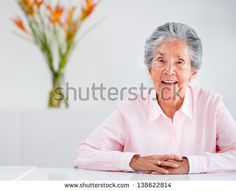 Beautiful elder woman at home looking very happy - stock photo