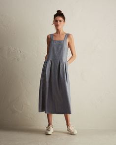 Supple, midweight linen with a woven crosshatch stripe. Pinafore top, front and back with pleated skirt below. Corozo shank buttons at left side.