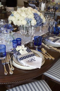 Monogrammed napkins and menus add the final touch to silver, white, and crystal place-settings.