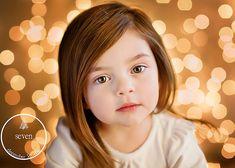 studio lights on face, background dark except holiday lights; Farrah Jobling Photography