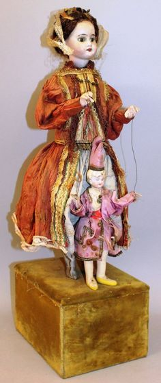 AN UNUSUAL FRENCH STANDING AUTOMATON PORCELAIN DOLL modelled in a period dress holding a bisque porcelain puppet.