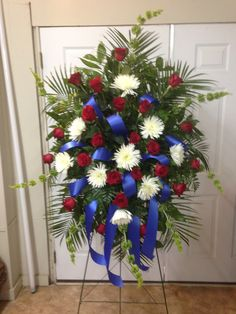 Live Funeral Spray using Bells of Ireland, white Fuji Mums, and Red Roses accented with Royal Blue Ribbon. Veteran Funeral. (Smith). October 2015