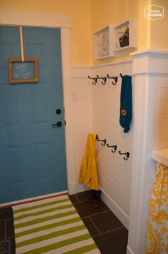 Laundry Room after horizontal white paneling turquoise chalkboard paint door and hooks at thehappyhousie