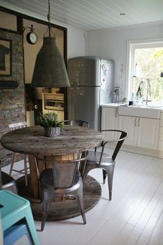 Zowie!  Really, who can be so lucky? The perfect use for a large wooden spool, a great vintage fridge, brick, industrial upcycled lighting, farm house sink, what did i miss? Oh the clock...lemme think...bliss.  The painted floors