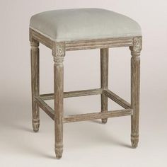 A sophisticated take on a classic, our exclusive backless counter stool is crafted of American white oak with carved details and a distressed finish. Velvety microfiber upholstery in a dove gray hue makes it a fine seating update for the home bar or kitchen.