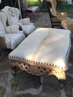 Coffee table turned large ottoman - upholstered with white cowhide and large nailheads.