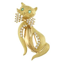 This charming brooch features a cat design with glistening emerald eyes and round-cut diamonds. This estate jewelry is crafted of 18-karat yellow gold with a highly polished finish.