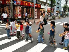 Japanese school children.    When a bunch of Japanese school children cross the road, you will  often see them raise their hand like so.