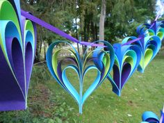 These two peacock garlands are just the thing to decorate any wedding, shower, or event. Or use them to decorate a childs bedroom. Or an office. They make great gifts too! This listing is for two strings of layered hearts, in peacock colors: Turquoise, Royal Blue, Purple, Chartreuse, Teal Blue, and a Dark Blue. There are 5 hearts on each strand. The hearts are punched with a hole and hung on a long ribbon. Each heart measures about 5 x 5 inches and is 1.5 deep. You can clump them together or…