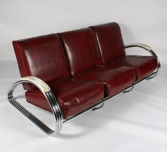 Kem (Karl Emmanuel Martin) Weber (1889-1963) Art Deco triple band sofa with burgundy vinyl upholstery. Weber designed this American art deco triple band sofa and two chair set for Lloyd Manufacturing Company in 1934. The set is featured in Lloyd\'s 1937 and 1938 catalogs.  Production of this furniture ceased in 1941 with the onslaught of World War II. Original pieces are nearly impossible to find and condition is often poor.
