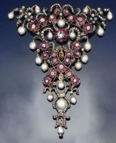 A diamond and gem stomacher brooch  of shaped triangular openwork hinged form, set throughout with old-brilliant-cut diamond and ruby flowerhead clusters, with rose-cut diamond floral scroll decoration, old-brilliant-cut diamond bud detail, cultured pearl drops and single stone detail, and marquise and brilliant-cut brown diamond accents