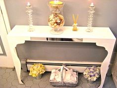 You can build a slim, feminine Console Table that's ideal for a petite bathroom with an Ikea LACK Wall Shelf ($19.99) and two VIKA FINTORP legs ($10 each). Total price $40.00. Begin by painting them white. If you want extra polish, have them powder-coated. Simply screw the legs into the shelf and fasten the table to the wall. Accessorize your table with candles, a hurricane filled with potpourri, & a basket to hold guest towels. Tin can to hold flowers for an Industrial-Chic look!