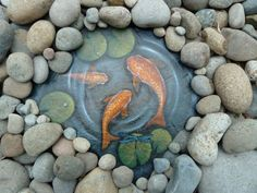 Water scene painted on slate, surrounded by river rock, looks cool!