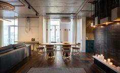 Luminaire industriel, plafond en béton brut et casier à bouteilles en bois dans un appartement à Kiev