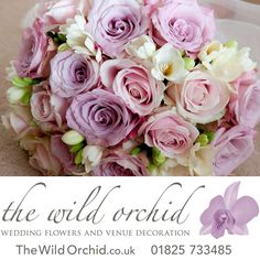 Handtied bridal bouquet of roses and scented freesia tied with vintage lace.
