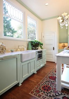 Chic+vintage+green+kitchen+design+with+mint+green+kitchen+cabinets,+green+crown+molding,+farmhouse+sink,+marble+counter+tops,+white+kitchen+island+and+subway+tiles+backsplash.