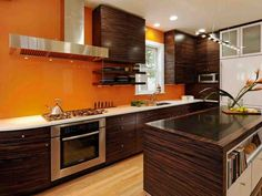 Brown cabinets and a matching kitchen island with a fun, unconventional print are featured in a contemporary orange kitchen. Burnt Orange Kitchen, Orange Kitchen Decor, Orange Kitchen Walls, Kitchen Cabinets And Countertops, Kitchen Backsplash, Backsplash Ideas, Kitchen Cupboards, Bathroom Cabinets, Brown Cabinets