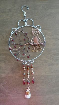 Wire wrapped beaded sun catcher with gold stone owl on crab apple tree branch.