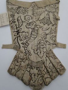 Lining, stomacher, early 18th century, inner part dating c. mid 17th century. Cream silk with floral embroidery in polychrome silk threads, edges and front flap are bound in silk criss crossed cord, linen lining with a design of undulating vines, acorns of fruit and leaves.
