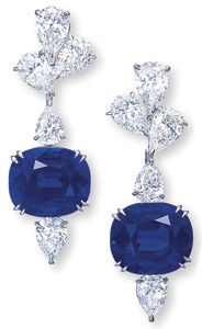 A pair of ear pendants featuring cushion-shaped Kashmir sapphires weighing 14.84 carats and 13.47 carats, suspended from pear-shaped diamond clusters