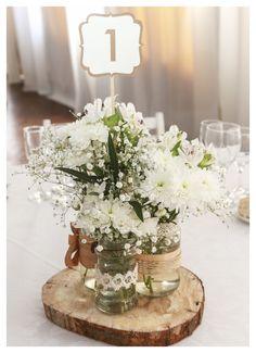Centros de mesa. Mandamos a cortar rodajas de madera y optamos por frascos de vidrio de diferentes tamaños y formas reciclados. Flores blancas de distinto tipo.