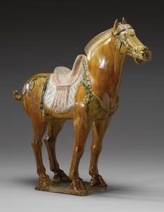 AN AMBER-GROUND 'SANCAI'-GLAZED POTTERY HORSE  TANG DYNASTY