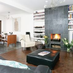 A slate-fronted floor-to-ceiling fireplace is complemented by simple white shelving on either side, making modern use of traditional alcoves.