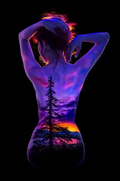 Lone Pine - A pine tree silhouette against a mountain lake sunset painted on a woman's back using fluorescent bodypaint and photographed under blacklight.