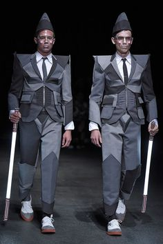 Thom Browne's Spring/Summer 2015 menswear collection. Models/guards in an armour-like wool suit (slightly reminiscent of the Cubist costumes by Jeffrey Bryant for the Pet Shop Boys) and carrying laser sabers opened the show.