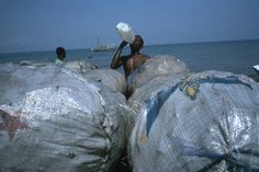 Alex Webb  HAITI. Leogane. 2000. Bags of charcoal on the beach. Worker drinking.