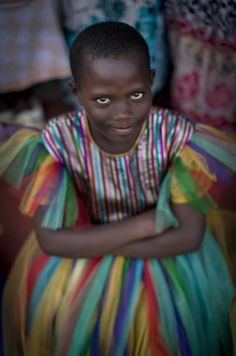 A young Rwandan girl sits amongst hundreds gathered at a ceremony to await the arrival of a small flame of remembrance, symbolic fire traveling the country, and hear genocide memories in the capital Kigali, Rwanda on April 5, 2014. (Ben Curtis/AP)