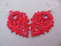 Red lace earrings with glass bead enhancements. Frivolité lace design is lightweight and intricate. Casual or evening wear, add sparkle with these earrings. I created these original design earrings using a small tatting shuttle, in the French style, and glass seed beads on strong polyester thread. About 140 red color glass seed beads are knotted (tatted) onto red polyester and purple metallic thread to create an intricate interplay of patterns and texture. A silver color French ear wire…