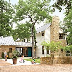 """Architect Tim Cuppett designed a new farmhouse accented with imperfectly layered Texas limestone. The purposely rambling plan looks like it was added onto over time. A windowed entry connects two structures in the spirit of a Southern dogtrot, yet the floor-to-ceiling glass gives it an updated feel. """"So many of the elements on this house are familiar—white clapboard, metal roof, stacked-stone chimney,"""" says Executive Editor Jessica Thuston."""